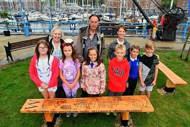 Teacher Delyth Evans, sculptor Robert Graves, Tourism Manager at the Port of Milford Haven Karen Lewis and pupils from Gelliswick VC School unveil the new benches at Milford Waterfront