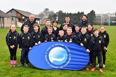 : Emma Hutchings, PR and Communications Assistant at the Port, with members of Pembroke Dock RFC Under 9's team in their new tour hoodies